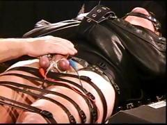 Totally bound hunk in leather straitjacket in CBT with high voltage stim to balls as he's jacked off