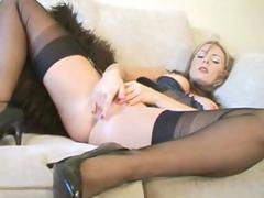 Blonde in latex and black stockings strips and masturbates