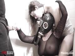 Strange women in gas mask plays with another woman before sucking cock