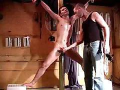Slave is tied up and his master is playing with his poor cock