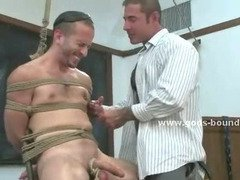 Muscular man wrapped in latex is tied up flogged and has his body covered in clothes pins