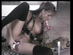 Sexy blond in leather uses a big dildo on her wet pussy