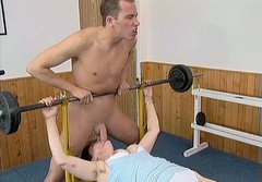 Mature brunette giving a blowjob to her coach right in the gym