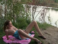 Blonde teen masturbates on the lake shore