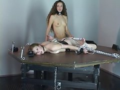 Brunette slave is bound with rope to table
