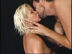 Blonde temptress is fisted and fucked by two cocks in black room