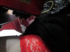 Flashing black stockings with red tops under the table