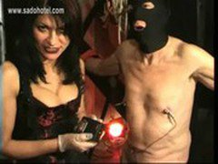 Beautiful mistress with big tits pulls meat hook through nipples of naughty slave and spanks him