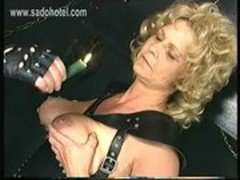Hot older slave with big tits wearing leather got hot candle wax on her boobs and is spanked