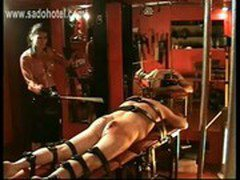 Brunette Mistress in latex skirt hits tied up slave on his ass with a stick till its bleeds