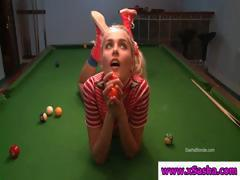 Cute little blonde teen is playing around and posing on a pool table